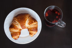 Fresh and tasty bavarian croissant on white plate and a glass of fruit tea over wooden background Royalty Free Stock Photo