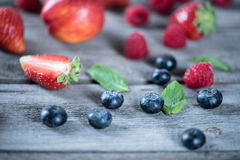 Fresh tasty berries with green leaves on wooden table Royalty Free Stock Photo