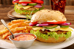 Fresh tasty burger with fries and drink on wooden table Royalty Free Stock Photos