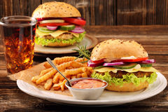 Fresh tasty burger with fries and drink on wooden table Royalty Free Stock Images