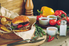 Fresh tasty burgers with french fries, sauce and ingredients on the wooden table top Royalty Free Stock Images