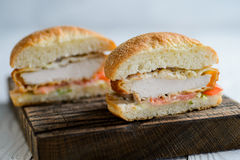 Fresh tasty chicken burger sectional view. On wooden table Royalty Free Stock Photos