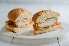 Fresh tasty chicken burger sectional view. On wooden table Stock Photo