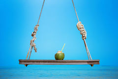 Fresh tasty coconut on a swing at tropical sea background Stock Photography
