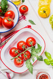 Fresh tasty colorful tomatoes in enamelled bowls on light kitchen table, ready for cooking or salad making. Top view Stock Images