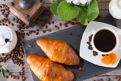 Fresh and tasty croissant on dark stone plate with cup of aroma coffee, jug of cream to coffee and flowers. Top view. Fresh and tasty croissant on a dark stone Stock Photos