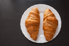 Fresh and tasty croissant on white plate over wooden background Stock Photography