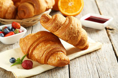 Fresh tasty croissants. With berries on grey wooden background Stock Photo