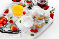 Fresh tasty donuts with ripe berries and raspberries jam on white wooden board. Stock Image
