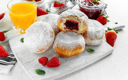 Fresh tasty donuts with ripe berries and raspberries jam on white wooden board. Stock Photography