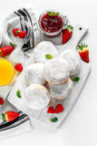 Fresh tasty donuts with ripe berries and raspberries jam on white wooden board. Royalty Free Stock Photo
