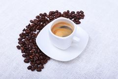 Fresh tasty espresso cup of hot coffee with coffee beans on white background. Royalty Free Stock Photos