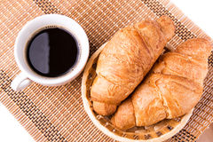 Fresh and tasty French croissants in a basket and cup of coffee served Royalty Free Stock Photo