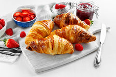 Fresh tasty homemade croissants with ripe berries and raspberries jam on white wooden board.  Royalty Free Stock Photography