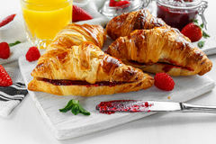 Fresh tasty homemade croissants with ripe berries and raspberries jam on white wooden board.  Royalty Free Stock Photo
