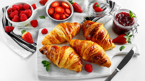 Fresh tasty homemade croissants with ripe berries and raspberries jam on white wooden board Stock Images