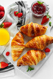 Fresh tasty homemade croissants with ripe berries and raspberries jam on white wooden board Royalty Free Stock Photography