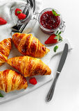 Fresh tasty homemade croissants with ripe berries and raspberries jam on white wooden board Royalty Free Stock Photo