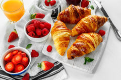 Fresh tasty homemade croissants with ripe berries and raspberries jam on white wooden board.  Royalty Free Stock Photos