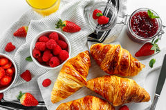 Fresh tasty homemade croissants with ripe berries and raspberries jam on white wooden board Stock Photography