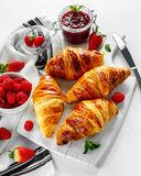 Fresh tasty homemade croissants with ripe berries and raspberries jam on white wooden board Stock Photos