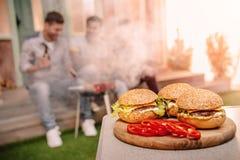 Fresh tasty homemade hamburgers on wooden cutting board Royalty Free Stock Photo