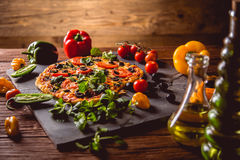 Fresh and tasty homemade pizza on wooden table with ingredients Stock Images