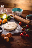 Fresh and tasty homemade pizza on wooden table with ingredients Stock Photo