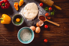 Fresh and tasty homemade pizza on wooden table with ingredients Royalty Free Stock Image