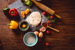Fresh and tasty homemade pizza on wooden table with ingredients Stock Photos