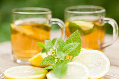 Fresh tasty hot tea lemon and mint outdoor in summer Royalty Free Stock Photo