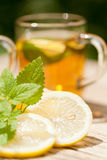 Fresh tasty hot tea lemon and mint outdoor in summer Stock Images