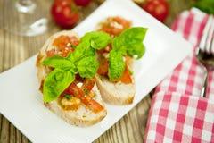 Fresh tasty italian bruschetta with tomato on table Royalty Free Stock Images