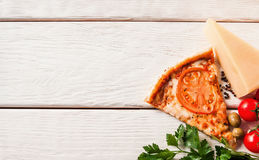 Fresh tasty italian pizza. Fast food background. Slice of tasty pizza with ingredients in the corner of white wooden table, top view. Background with free space Royalty Free Stock Image