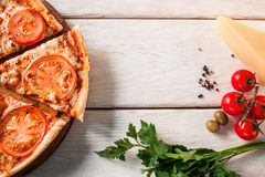 Fresh tasty italian pizza. Fast food background. Sliced baked pizza on white wooden background with free space, top view. Table decorated with parsley, green Stock Images