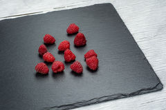Fresh and tasty looking raspberries on a wooden table.  Royalty Free Stock Photos