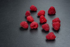 Fresh and tasty looking raspberries on a wooden table.  Stock Image