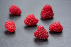 Fresh and tasty looking raspberries on a wooden table.  Royalty Free Stock Photography