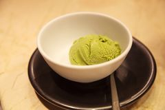 Fresh tasty matcha green tea flavored ice cream served in white bowl on table background. Healthy sweets, summer desserts, royalty free stock photography