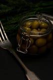 Fresh tasty olives dark with dill vintage fork selective focus dark photo Stock Photos