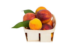 Fresh tasty peaches. With green leaves in wooden box -  on white background Royalty Free Stock Images