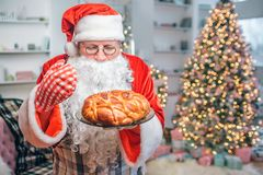 Fresh and tasty pie is in hands of Santa Claus. He looks at it and smells. There are Christmas tree behind him. Fresh and tasty pie is in hands of Santa Claus stock image