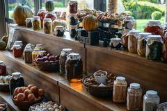 Fresh tasty pumpkins and preserved and pickled seasonal vegetables and honey in glass jars and on baskets on the brown w stock photography