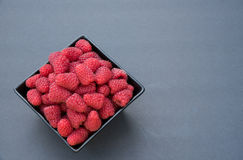 Fresh tasty raspberries. Fresh raspberries in a black bowl, on a black background Stock Image
