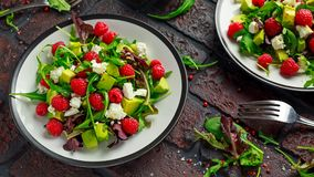 Fresh Tasty Raspberry salad with avocado, green vegetables, nuts, feta cheese, olive oil and herbs. healthy food. Fresh Tasty Raspberry salad with avocado Stock Photos