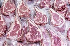 Fresh tasty raw beef steaks with bone wrapped in vacuum plastic. Packing at market or shop Stock Images