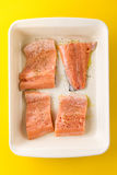 Fresh tasty raw salmon slices in baking form ready to bake on ye. Llow vibrant background. Above Top View. Design Stock Photos