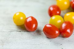 Fresh tasty red and yellow tomatoes. On wooden background closeup Royalty Free Stock Images