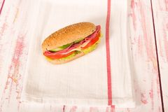 Sandwich with cheese, tomato, salami, cucumber and lettuce on wo. Fresh and tasty sandwich on cloth napkin Royalty Free Stock Photo