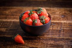 Fresh tasty strawberries in a black cup on a wooden table. Strawberry on the table next to cup of berry. Fresh tasty strawberries in a black cup on a wooden Royalty Free Stock Photos